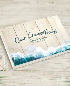 A beautiful Beach Themed Wedding Guestbook Guestbook that includes your personalised text on the cover. The cover features a sea coast photo on a wood look background. The background image has the style of wood, but is not textured.
